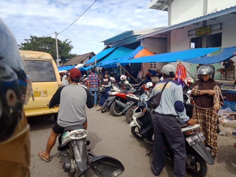 Seorang berpakaian Dishub (perhatikan sebelah kanan) tengah mengurus parkiran motor. Seorang 'emak-emak' hendak membayar biaya parkiran.